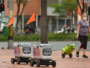 Robot pengiriman berjalan menyusuri jalan di Medellin, Kolombia, Selasa (21/4/2020). Perusahaan rintisan Kolombia, Rappi, menguji coba pengiriman dengan robot sebagai cara aman mendapatkan makanan bagi masyarakat yang terpaksa berada di rumah akibat pandemi virus corona Covid-19. (AP/Luis Benavides)