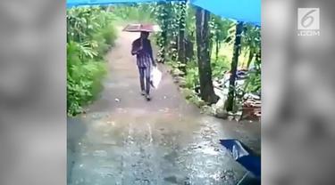 Ada-ada saja yang dilakukan pria ini agar anaknya tak kehujanan. Ia menaruh sang anak didalam kantung plastik dan menentengnya sepanjang jalan.