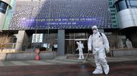 Petugas menyemprotkan disinfektan di depan Gereja Shincheonji di Daegu, Korea Selatan, Kamis (20/2/2020). Korea Selatan resmi menjadi negara terbesar yang melaporkan jumlah kasus virus corona atau COVID-19 di luar China. (Kim Jun-beom/Yonhap via AP)