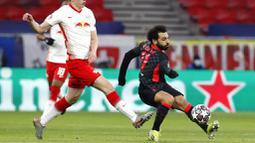 Striker Liverpool, Mohamed Salah, menendang bola saat melawan RB Leipzig pada laga Liga Champions di Stadion Puskas, Rabu (17/2/2021). Liverpool menang dengan skor 2-0. (AP/Laszlo Balogh)