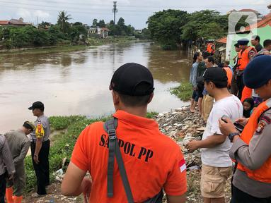 Warga bersama personel kepolisian, Satpol PP, dan TNI berkumpul di bantaran Sungai Ciliwung, Jakarta, Selasa (25/2/2020). Adanya warga yang hanyut saat berenang di tengah luapan Sungai Ciliwung mengundang perhatian warga dan petugas yang mencari keberadannya. (Liputan6.com/Immanuel Antonius)