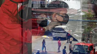 Pelanggan dipotong rambutnya oleh tukang cukur berpakaian alat pelindung diri (APD) yang tercermin di sebuah jendela di Manila, 8 Juni 2020. Filipina mengizinkan barbershop dan salon kecantikan beroperasi kembali dengan menerapkan langkah-langkah ketat pencegahan pandemi Covid-19. (AP/Aaron Favila)