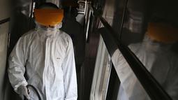 Petugas melakukan penyemprotan disinfektan pada gerbong kereta api di Stasiun Pasar Senen, Jakarta, Minggu (15/3/2020). PT KAI Daop I Jakarta melakukan penyemprotan disinfektan dan pembersihan KA jarak jauh untuk antisipasi dan pencegahan penyebaran COVID-19. (Liputan6.com/Herman Zakharia)