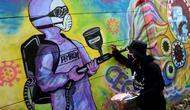 Warga melukis mural bertema COVID-19 di kawasan Tanah Tinggi, Tangerang, Banten, Rabu (20/1/2020). Kegiatan ini dalam rangka mensosialisasikan bahaya penyebaran COVID-19 kepada warga pengguna jalan umum. (merdeka.com/Arie Basuki)