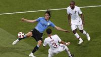 Aksi penyerang Uruguay, Edinson Cavani (kiri) melepaskan tembakan melewati adangan dua pemain Portugal pada laga 16 besar Piala Dunia 2018 di Fisht Stadium, Sochi, Rusia, (30/6/2018). Portugal kalah 1-2. (AP/Darko Vojinovic)