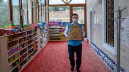 Imam masjid Dedeman, Abdulsamet Cakir membawa barang-barang di pintu masjid di distrik Sariyer, Istanbul pada 21 April 2020. Jelang Ramadan, masjid itu membuka supermarket gratis yang menyediakan kebutuhan sehari-hari secara gratis untuk warga membutuhkan yang terdampak Corona. (Bulent Kilic/AFP)