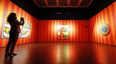 Pengunjung mengamati karya seni seniman Amerika Serikat Keith Haring saat pameran di Museum Folkwang, Essen, Jerman, Selasa(1/9/2020). Keith Haring merupakan seniman jalanan asal New York yang meninggal akibat komplikasi AIDS pada tahun 1990. (AP Photo/Martin Meissner)