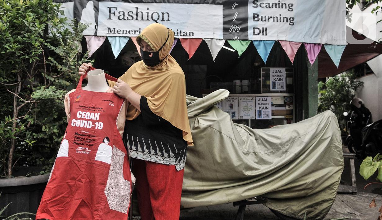 Siti Zahro (44) memajang celemek berbahan tas bansos Covid-19 buatannya di depan industri jahit rumahan KG-Lupe Fashion, Salemba, Jakarta, Senin (16/11/2020). Inovasi Siti bermula dari sepinya pesanan jahit akibat pandemi. (merdeka.com/Iqbal S. Nugroho)