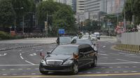 Iring-iringan mobil yang diyakini membawa pemimpin Korea Utara Kim Jong-un melewati Orchard Road menuju St Regis Hotel di Singapura, Minggu (10/6). Kedatangan Kim menjelang pertemuan bersejarah dengan Donald Trump pada Selasa mendatang. (AP/Joseph Nair)