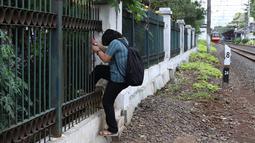 Warga menerobos pagar usai menyeberangi rel kereta api di kawasan Lenteng Agung, Jakarta, Selasa (19/3). Tidak adanya JPO menyebabkan warga harus menerobos pagar besi, meskipun perilaku tersebut berbahaya bagi keselamatan. (Liputan6.com/Immanuel Antonius)