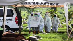 Petugas membawa jenazah presenter Rina Gunawan saat prosesi pemakaman di TPU Tanah Kusir, Jakarta, Rabu (3/3/2021). Pihak keluarga belum menyebutkan penyebab dari meninggalnya perempuan bernama lengkap Rina Mustikana Gumilang Gunawan tersebut. (Kapanlagi.com/Budy Santoso)