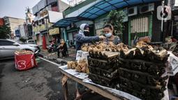 Pedagang melayani pembeli ketupat matang di jalan kawasan Rawamangun, Jakarta, Senin (19/7/2021). Jelang Hari Raya Idul Adha, pedagang ketupat matang atau siap saji musiman mulai ramai menjajakan makanan khas Lebaran tersebut di pinggir jalan kawasan Rawamangun. (merdeka.com/Iqbal S. Nugroho)