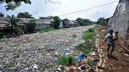 Warga melintas di pinggir Kali Pisang Batu yang dipenuhi sampah, Tarumajaya, Bekasi, Rabu (9/1). Tumpukan sampah tersebut berasal dari limbah rumah tangga. (Merdeka.com/Iqbal S Nugroho)