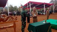 Penyerahan draft program TMMD ke 103 dari Bupati Garut Rudy Gunawan ke Dandim 0611 Garut Letkol Asyraf Aziz (Liputan6.com/Jayadi Supriadin)