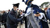 Seorang polisi yang mengenakan masker sanitasi mengontrol dengan detektor logam pada acara karnival di Venesia, Minggu, 23 Februari 2020. (AP/ Luigi Costantini)