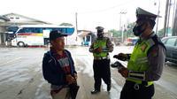 Aparat kepolisian memberikan masker gratis dan edukasi secara masif kepada para penumpang di pool bus Sinar Jaya, Jalan Inspeksi Kalimalang, Desa Suka Danau, Cikarang Barat, Kabupaten Bekasi, Jawa Barat. (Liputan6.com/Bam Sinulingga)