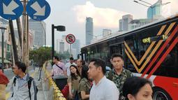 Warga menunggu angkutan umum di tepi Jalan Jenderal Sudirman, Jakarta, Senin (8/7/2019). Tidak adanya halte menyebabkan warga terpaksa menunggu angkutan umum di tempat seadanya. (Liputan6.com/Immanuel Antonius)