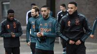 Gelandang Ajax, Hakim Ziyech (tengah) dan bek Noussair Mazraoui (kanan) tiba untuk menghadiri sesi pelatihan di Amsterdam (22/10/2019). Ajax akan bertanding melawan wakil Inggris, Chelsea pada Grup H Liga Champions di Johan Cruijff Arena. (AFP Photo/John Thys)