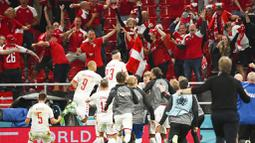 Para pemain melakukan selebrasi di depan para suporter Denmark usai peluit akhir pertandingan berbunyi. Mereka mengakhiri laga dengan kemenangan telak 4-1 atas Rusia. (Jonathan Nackstrand/Pool via AP)