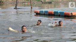 Anak-anak berenang di Kanal Banjir Barat, Jakarta, Minggu (3/11/2019). Mereka memilih berenang di Kanal Banjir Barat karena minimnya fasilitas bermain di kawasan tersebut. (merdeka.com/Iqbal Nugroho)