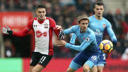 Bek Arsenal, Nacho Monreal, berebut bola dengan gelandang Southampton, Dusan Tadic, pada laga Premier League di Stadion St Mary's, Minggu (10/12/2017). Arsenal bermain imbang 1-1 dengan Southampton. (AP/Adam Davy)