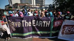 Aktivis Gerakan Muda FCTC membentangkan spanduk 'Save The Earth' saat melakukan Aksi Selamatkan Bumi dari Limbah Puntung Rokok di kawasan Bundaran HI, Jakarta, Minggu (26/4/2015). (Liputan6.com/Faial Fanani)