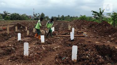 Petugas membersihkan area khusus pemakaman jenazah dengan protokol COVID-19 di TPU Srengseng Sawah Dua, Jakarta, Selasa, (2/2/2021). TPU Srengseng Sawah 2, saat ini mulai menerima pemakaman jenazah protokol COVID-19 dengan kapasitas 1.020 petak. (Liputan6.com/Helmi Fithriansyah)