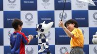 Seorang bocah berjabat tangan dengan robot maskot Olimpiade 2020, Miraitowa, pada acara hitung mundur setahun menjelang event tersebut, di Stadion Ajinomoto, Tokyo, Senin (22/7/2019). (AFP/Behrouz Mehri)