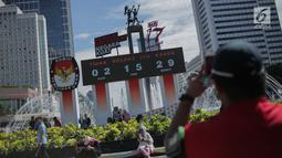 Warga memfoto  papan hitung mundur pelaksanaan Pemilu sebagai bagian dari sosialisasi di Bundara HI, Jakarta, Minggu (14/4). Papan tersebut dipasang bertujuan untuk mengingatkan sekaligus mengajak masyarakat untuk mengawasi proses demokrasi terbesar di Indonesia. (Liputan6.com/Faizal Fanani)