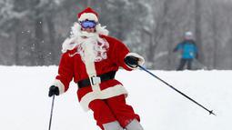 Pemain ski berpakaian Santa Claus menuruni lereng gunung saat Santa Sunday ke-19 di Newry, Maine, AS, Minggu (2/12). Keuntungan acara Santa Sunday digunakan untuk amal. (AP Photo/Robert F. Bukaty)