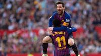 Penyerang Barcelona Lionel Messi memeluk rekan setimnya Ousmane Dembele usai mencetak gol ke gawang Sevilla pada laga La Liga di Stadion Ramon Sanchez Pizjuan, Sevilla, Sabtu (23/2). Barcelona menang 4-2. (JORGE GUERRERO/AFP)
