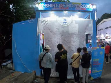 Sebuah kaus putih berukuran 3x3.1 meter menghiasi booth Koze Indonesia pada JakCloth Year End Sale 2019 di Plaza Tenggara GBK Senayan, Jakarta, Kamis (26/12/2019). Pengunjung membubuhkan tanda tangan dan harapan di tahun 2020. (Liputan6.com/Fery Pradolo)
