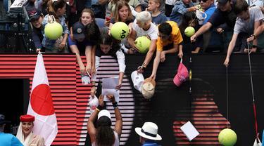 Petenis Jepang Naomi Osaka menandatangani benda yang disodorkan penonton usai mengalahkan petenis Republik Ceko Marie Bouzkova pada Australia Terbuka di Melbourne, Australia, Senin (20/1/2020). Penonton menyodorkan topi, bendera, hingga bola untuk ditandatangani Naomi. (AP Photo/Lee Jin-man)