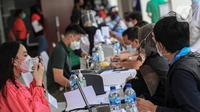 Petugas melakukan pendataan saat program vaksinasi COVID-19 kepada para atlet di Istora Senayan, Jakarta, Jumat (26/2/2021). Sebanyak 5.000 atlet diprioritaskan karena mereka dijadwalkan mengikuti beberapa kejuaraan single event maupun multievent dalam waktu dekat. (Liputan6.com/Faizal Fanani)