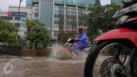 Pengendara motor melewati genangan air di kawasan Kuningan, Jakarta, Selasa (24/11). Jalur lambat di Jalan HR Rasuna Said, Kuningan, tampak dihindari pengendara karena terdapat genagan air setinggi 20 cm. (Liputan6.com/Faizal Fanani)