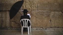 Orang Yahudi berdoa di Tembok Ratapan, situs paling suci di Kota Tua Yerusalem (16/2/2020). Ketika kekhawatiran tentang penyebaran virus corona meningkat, umat Yahudi yang setia mengadakan sesi doa untuk mencari intervensi ilahi untuk membantu mencegah penyakit tersebut. (AP Photo/Ariel Schalit)