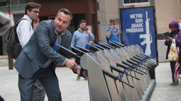 Seorang pria memegang senjata api yang merupakan instalasi seni dari Program Chicago Gun Share di Daley Center Plaza, Chicago, Illinois (14/5). (Scott Olson / Getty Images / AFP)