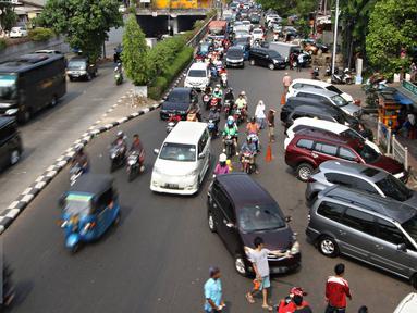 Kendaraan roda empat parkir di bahu Jalan Pramuka, Jakarta, Jumat (20/11). Banyaknya kendaraan pribadi yang parkir di kawasan tersebut menjadi salah satu penyebab kemacetan. terutama saat pagi hingga siang hari. (Liputan6.com/Immanuel Antonius)