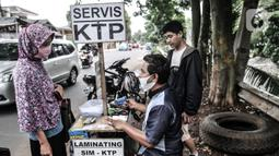 Feri (28) melayani pelanggan saat menyelesaikan jasa servis kartu tanda penduduk (KTP) di Jakarta, Kamis (21/1/2021). Feri mulai membuka jasanya sejak pukul 08.00 WIB hingga 17.00 WIB di pinggir jalan dengan lokasi yang tidak menetap alias berkeliling. (merdeka.com/Iqbal S. Nugroho)