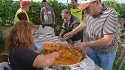 Relawan Tunisia membagikan makanan berbuka puasa gratis selama bulan suci Ramadan di Ariana dekat Tunis (7/5/2020). Masjid-masjid di Aljazair, Maroko dan Tunisia telah ditutup untuk membatasi penyebaran Covid-19, mencegah doa malam khusus. (AFP/Fethi Belad)