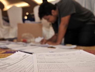 Operator menyortir form C1 saat mengentri data hitung cepat berbasis aplikasi Situng Pemilu 2019 se-Provinsi DKI Jakarta di Hotel Merlyn, Minggu (21/4). Entri data dan pindai form C1 Situng Pemilu 2019 wilayah Provinsi DKI Jakarta rata-rata telah mencapai 50 persen. (merdeka.com/Iqbal Nugroho)