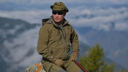 Presiden Rusia, Vladimir Putin berpose ketika menghabiskan waktu di kawasan hutan pegunungan Siberia, pada 6 Oktober 2019. Presiden Vladimir Putin menikmati hari lahirnya dengan mendaki pegunungan dan memetik jamur liar pada akhir pekan lalu. (Alexey DRUZHININ / Sputnik / AFP)