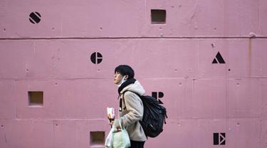 Seorang pria yang meletakkan masker wajah di bawah dagunya sambil makan makanan ringan berjalan melewati sekolah bahasa asing di Tokyo, Jepang,  Kamis (4 /2/2021). Tokyo mengonfirmasi lebih dari 730 kasus baru COVID-19 pada 4 Februari 2021. (AP Photo/Hiro Komae)