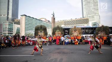 Pemain reog Ponorogo beraksi menghibur pengunjung di area car free day kawasan Bundaran Hotel Indonesia (HI), Jakarta, Minggu (28/4/2019). Kegiatan untuk memperingati Hari Kartini tersebut turut diramaikan oleh sejumlah polisi wanita (polwan). (Liputan6.com/Faizal Fanani)