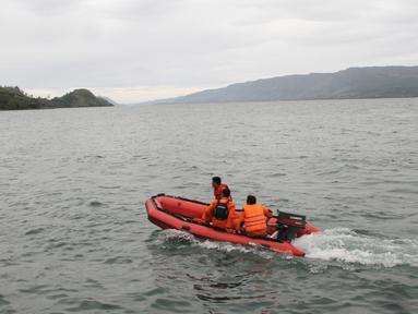 Tim penyelamat mencari korban hilang KM Sinar Bangun yang tenggelam di Danau Toba, Sumatera Utara, Selasa (19/6). Pencarian korban hilang sempat dihentikan akibat cuaca buruk. (AP Photo/Lazuardy Fahmi)