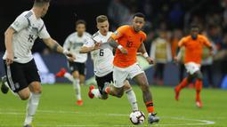 Penyerang Belanda, Memphis Depay, berusaha melewati bek Jerman, Joshua Kimmich, pada laga kualifikasi Piala Eropa di Stadion Johan Cruyff, Minggu (24/3). Belanda takluk 2-3 dari Jerman. (AP/Peter Dejong)
