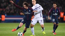 Gelandang PSG, Adrien Rabiot, berusaha melewati striker Anderlecht, Lukasz Teodorczyk, pada laga Liga Champions di Stadion Parc des Princes, Paris, Selasa (31/10/2017). PSG menang 5-0 atas Anderlecht. (AFP/Franck Fife)