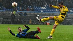 Bek Borussia Dortmund Marcel Schmelzer dan pemain Atalanta Alejandro Gomez berebut bola pada leg kedua babak 32 besar Liga Europa di MAPEI Stadium Citta del Tricolore , Jumat (23/2). Borussia Dortmund menahan imbang Atalanta 1-1. (Vincenzo PINTO/AFP)