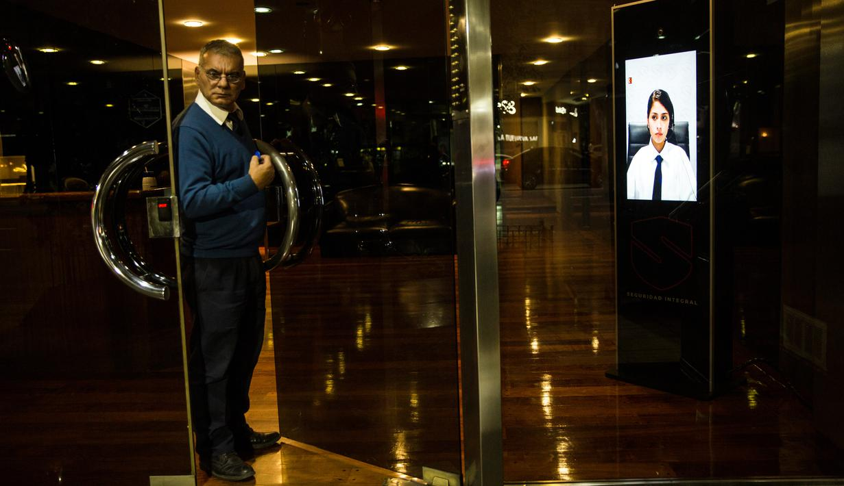 Seorang porter keluar dari pintu sebuah gedung di Buenos Aires, Argentina, Jumat (13/4). Argentina mulai menerapkan penjaga keamanan virtual di sujumlah gedung. (AP Photo/Rodrigo Abd)