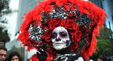 "Seorang wanita berpakaian seperti ""Catrina"" ambil bagian dalam parade catrinas atau Hari Orang Mati di Reforma Avenue, Mexico City, 21 Oktober 2018. Hari kematian ini merupakan tradisi Halloween ala warga Hispanik di Meksiko. (RODRIGO ARANGUA/AFP)"